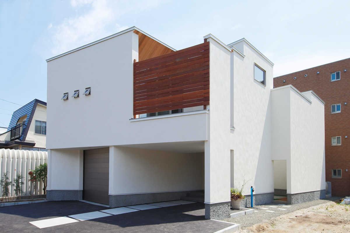 ビルトインガレージを採用したシンプルなデザインの外観に、ウッドフェンスのレッドが効いている