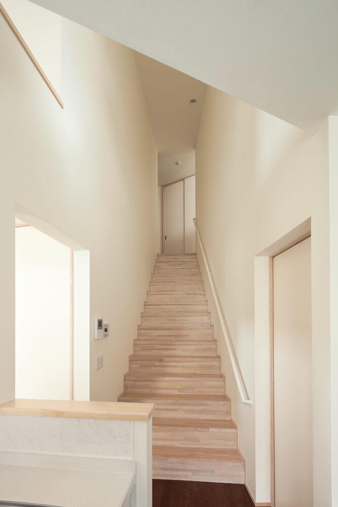1階から2階への移動はキッチン横の階段から。階段の幅は上に行くほど少しずつ狭くなり、視覚的に長さを感じるような仕掛けがなされている