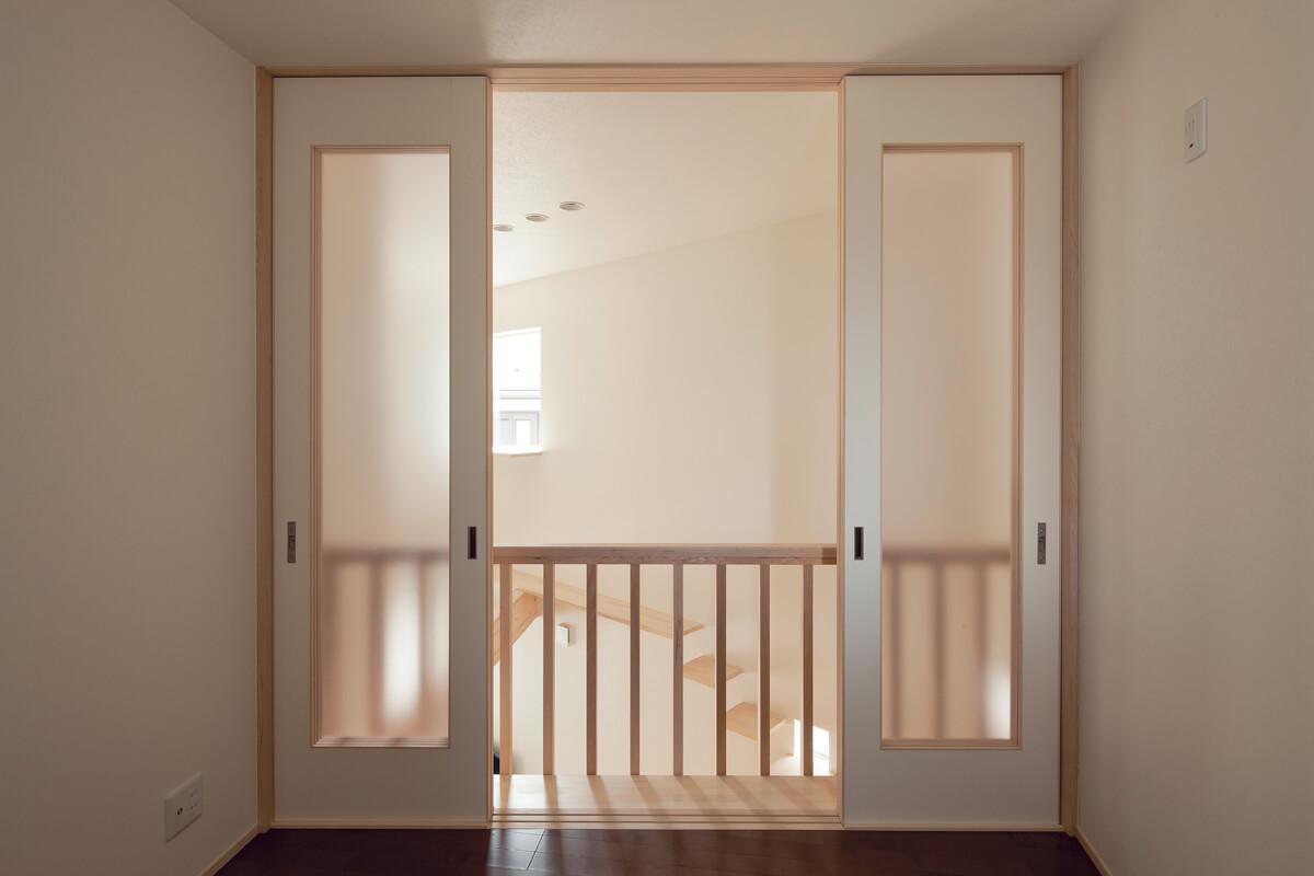 2階の洋室2。間仕切りを開放すると棚によって階下とつながる不思議な部屋に