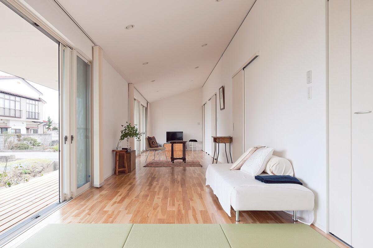 LDK奥の畳コーナーから室内を見返す。片流れの屋根形状をそのまま現すことで、凹凸のないシンプルな矩形に変化が生まれている
