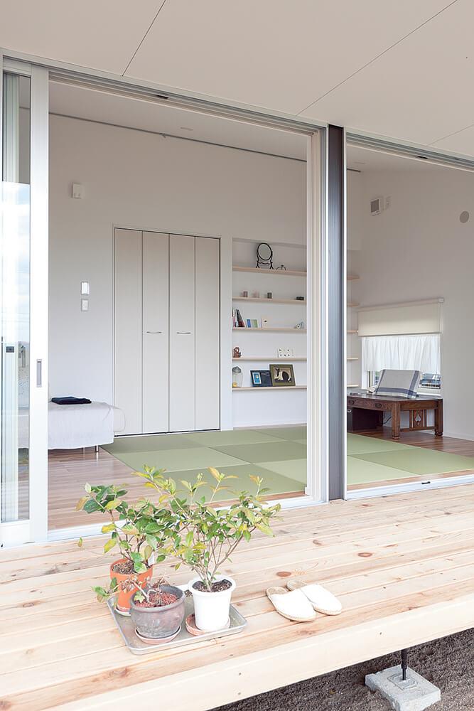 細長いLDKに沿うように設置したウッドデッキ。深い軒に守られた半屋外空間が室内外のつながりを深め、空間に広がりを与えてくれる