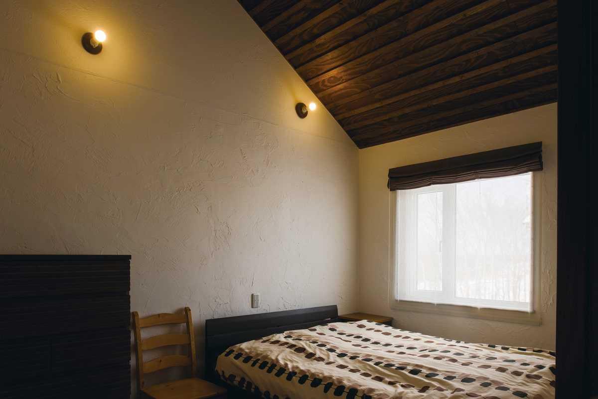 木張りの勾配天井と温かみのある塗り壁の風合いがやさしい寝室は、まるで森の中のペンションのよう