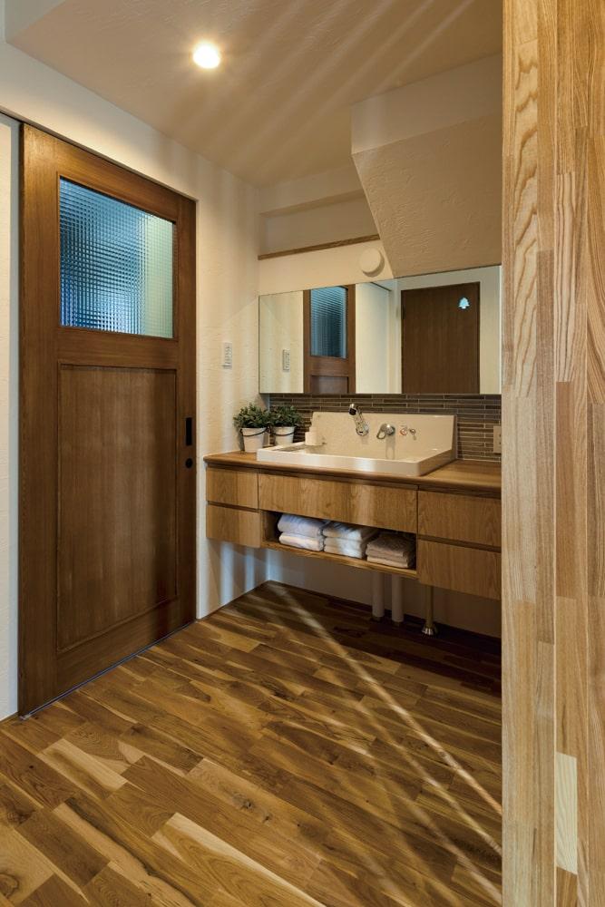 横長の鏡があるホテルのような洗練された雰囲気の洗面スペース。来客時を考えユーティリティからは独立させた 右左:ご夫妻が希望した広々とした玄関スペース
