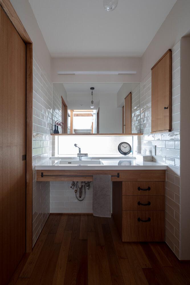 両サイドの壁を白い艶のあるタイルで仕上げた洗面台