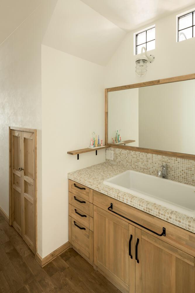 やさしいニュアンスに仕上げた洗面台の上部には、ヴィンテージ感のあるデザイン窓を明り取り窓として設置