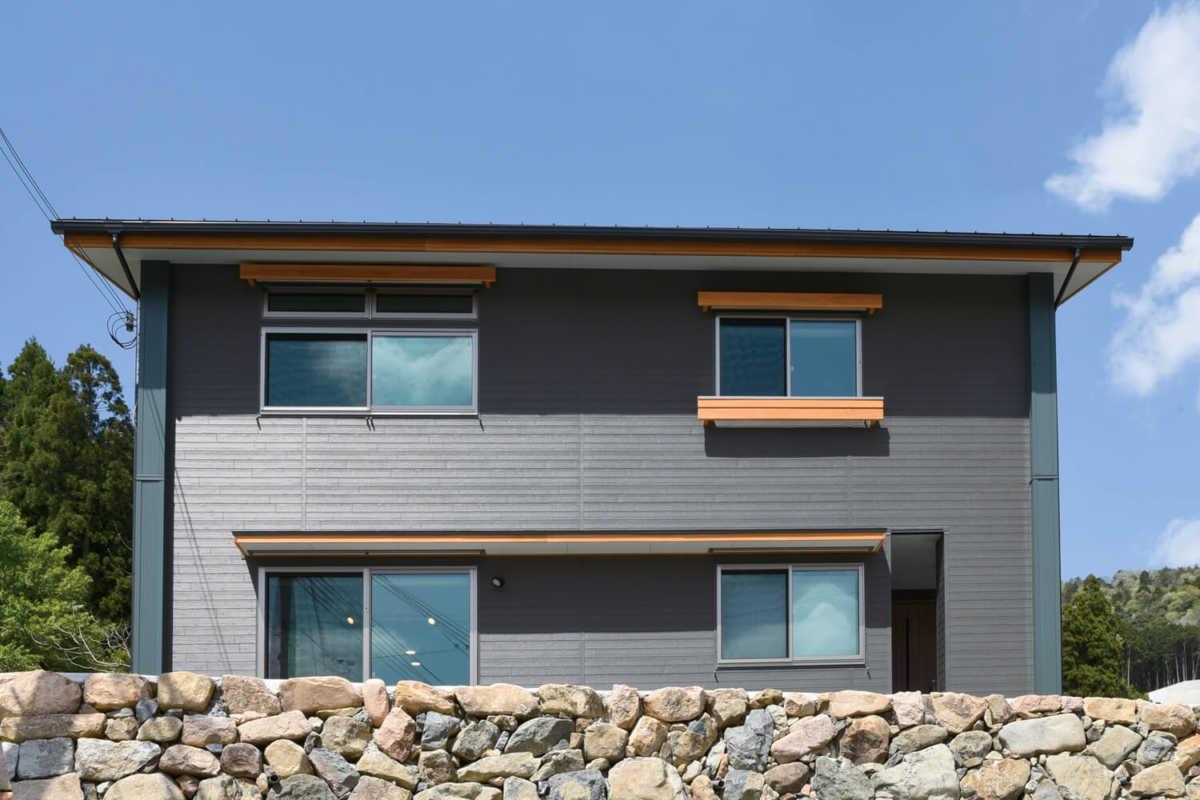 真南に向け深めの軒と外用スクリーンで夏の日射を防ぐシンプルな外観