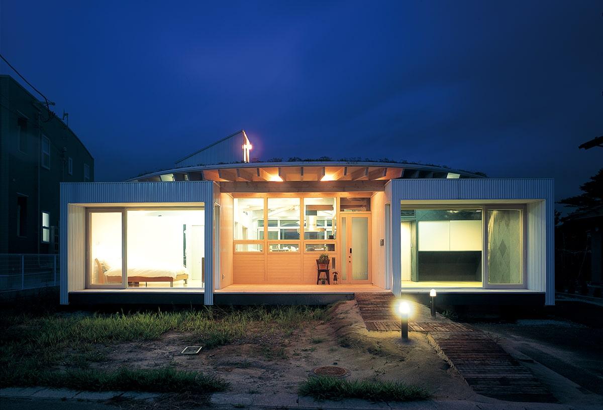 南側外観の夕景。放射状に組まれた垂木と垂木の間から、ガラスを通して室内の明かりがもれる