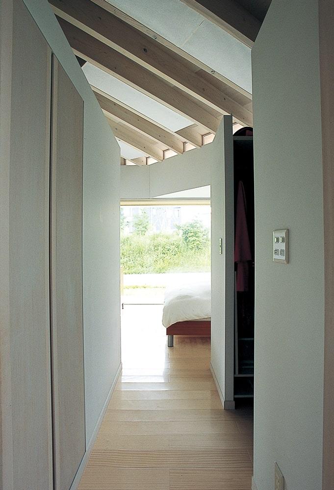 南側に面した主寝室。手前がクローゼット。放射状の天井垂木が空間に変化を与え、豊かな表情をつくる