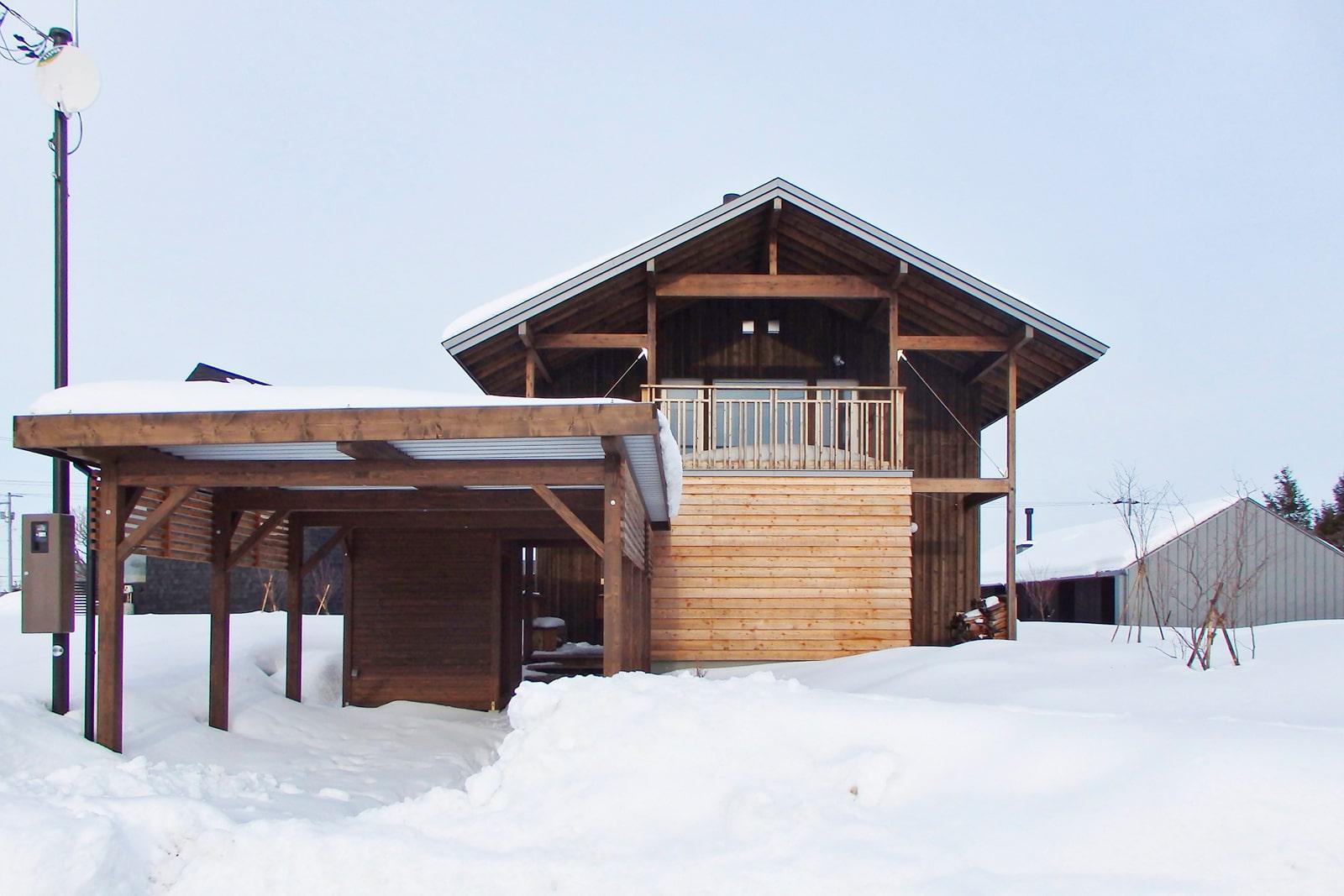 武部建設×アトリエmomo「てまひまくらし」 三角形の大屋根とカラマツ材を使った外壁が目をひく。カーポートも木でつくっている