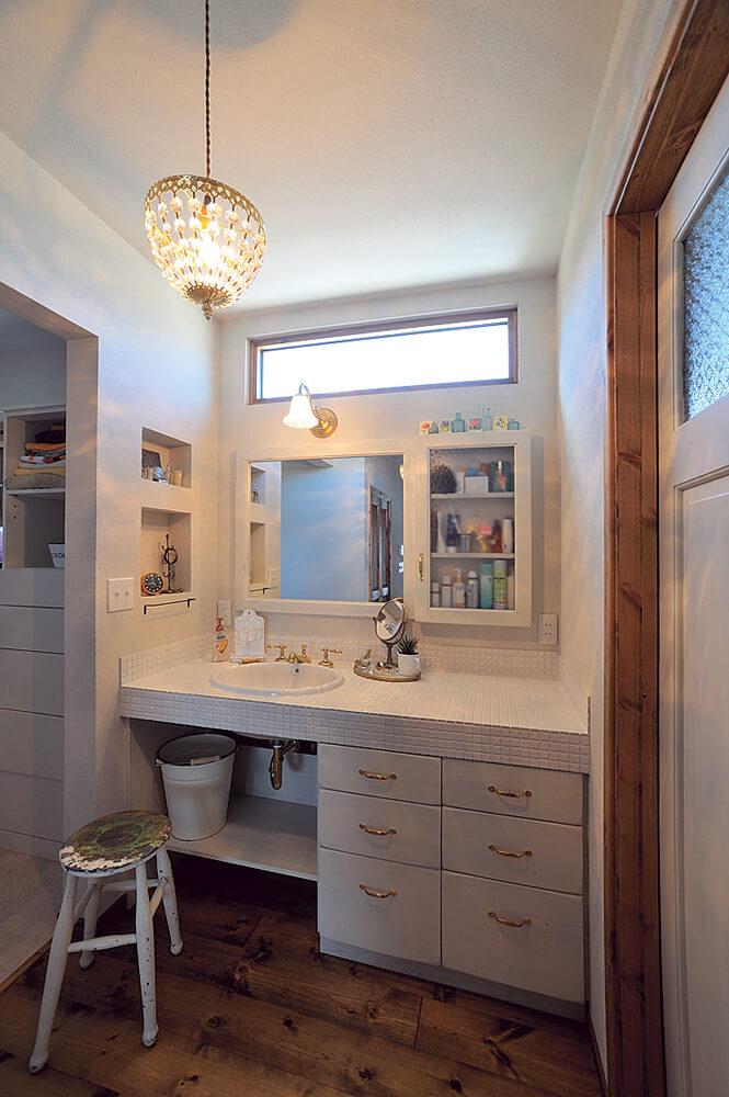 女性がメインで使う洗面は白を中心に清潔感あふれる空間に。カランや照明など、一つひとつのセレクトにこだわりがある