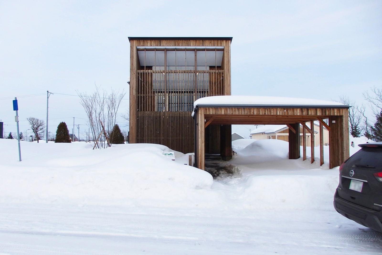 アシスト企画×山本亜耕建築設計事務所「南幌まちなかの家」<br /> 半屋外的空間として利用できるテラスと1階部分を覆う縦格子が印象的。2台分のカーポートと物置も設置