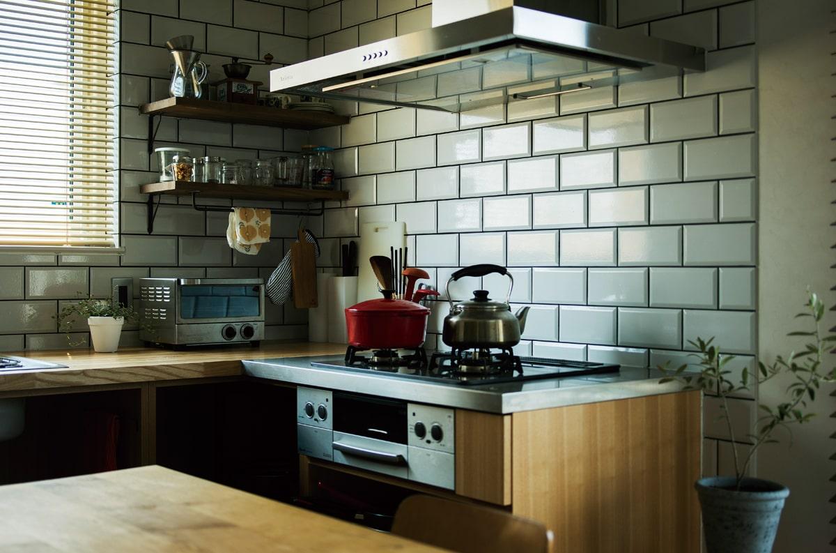 奥さんのこだわりが凝縮され、「ここにいるのが楽しいです」というダイニングキッチン。あえてシステムキッチンではなく、L型の木製カウンターを採用。ブリックタイルの目地は検討を重ねて、締まりのある黒に。調理器具などの小物と相まって味わい深い空間となっている
