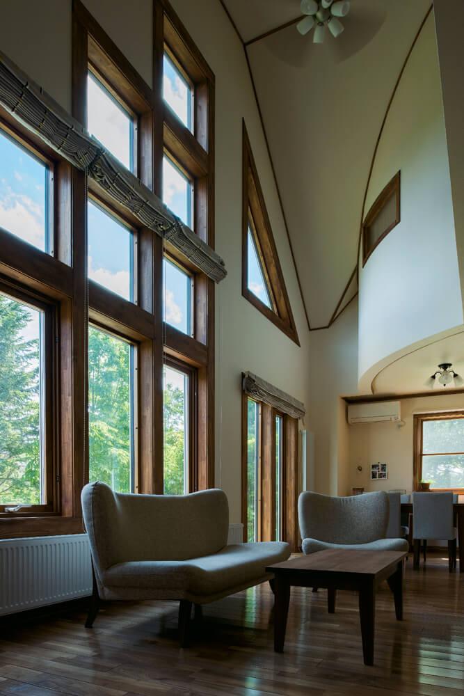 屋根なり天井と連続開口を設けた吹き抜けが、この上ない開放感を生み出すリビング・ダイニング。吹き抜けのアール壁の向こうは主寝室