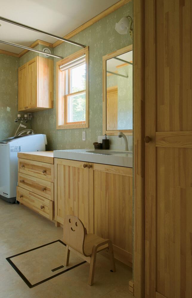造作洗面台を採用したユーティリティは玄関とLDKにつながる回遊動線を採用。シックな花柄の壁紙も奥さんのお気に入り