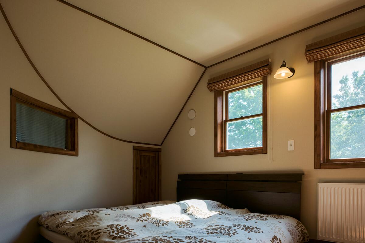 屋根なり天井にクラシカルな木製窓が落ち着いた雰囲気を演出する主寝室。ベッド脇の扉は、小さな造作収納