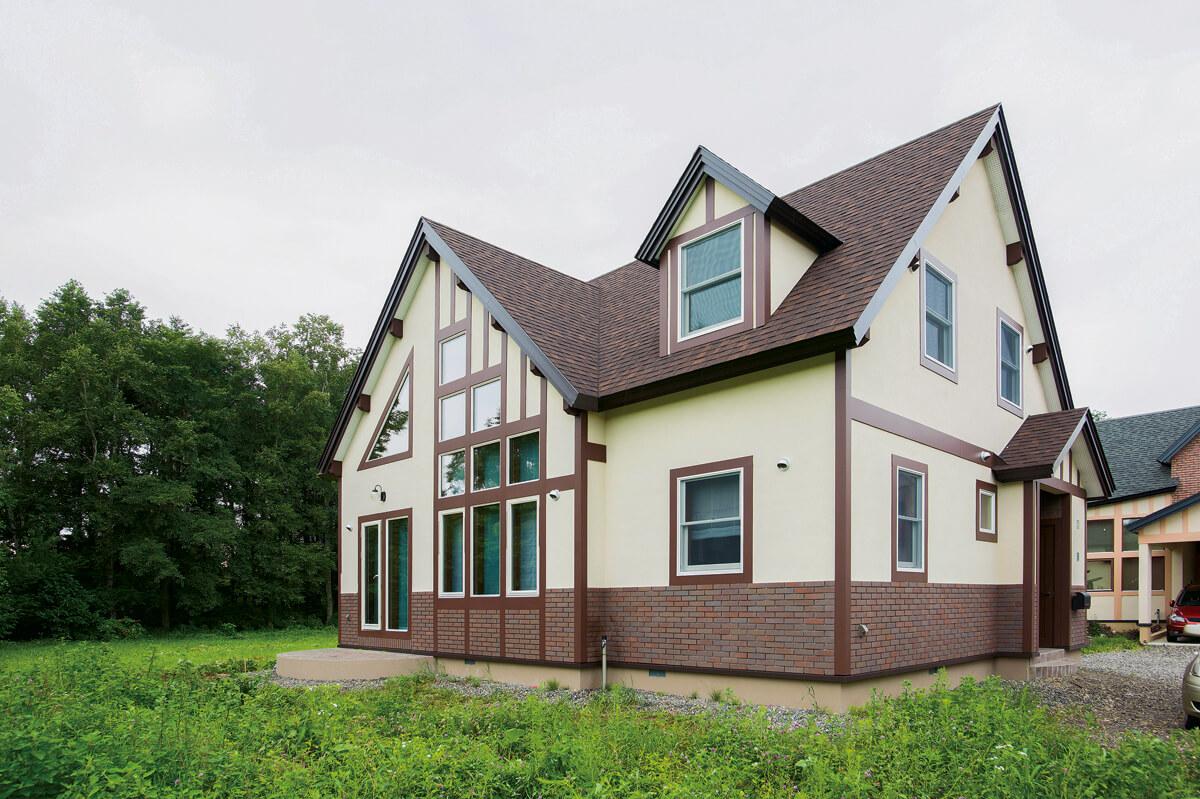 豊かな緑を背景に建つSさん宅は、大小の三角屋根と、クリーム色の外壁に幾何学模様を描く開口部が印象的な佇まい