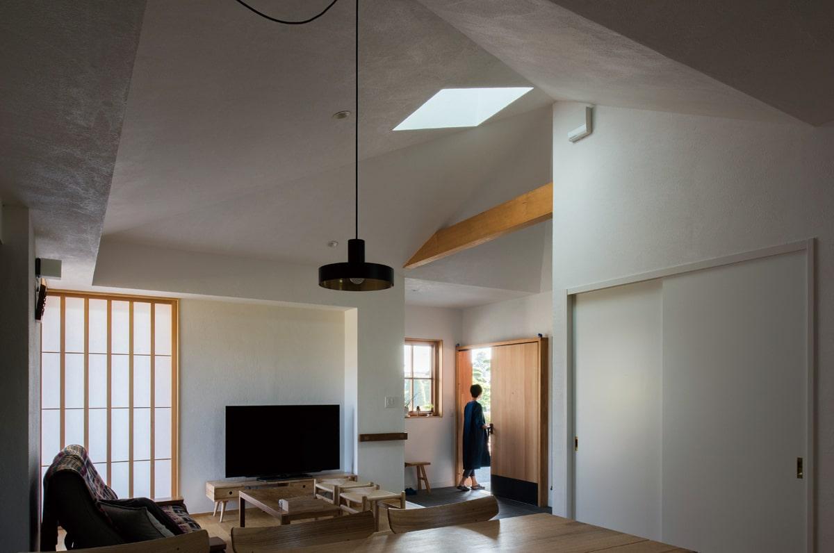 勾配天井のトップライトから優しい光が降り注ぐ。壁や天井はホタテの貝殻入りの漆喰仕上げで、凹凸のある独特のテクスチャーが美しい陰影をつくりだしている