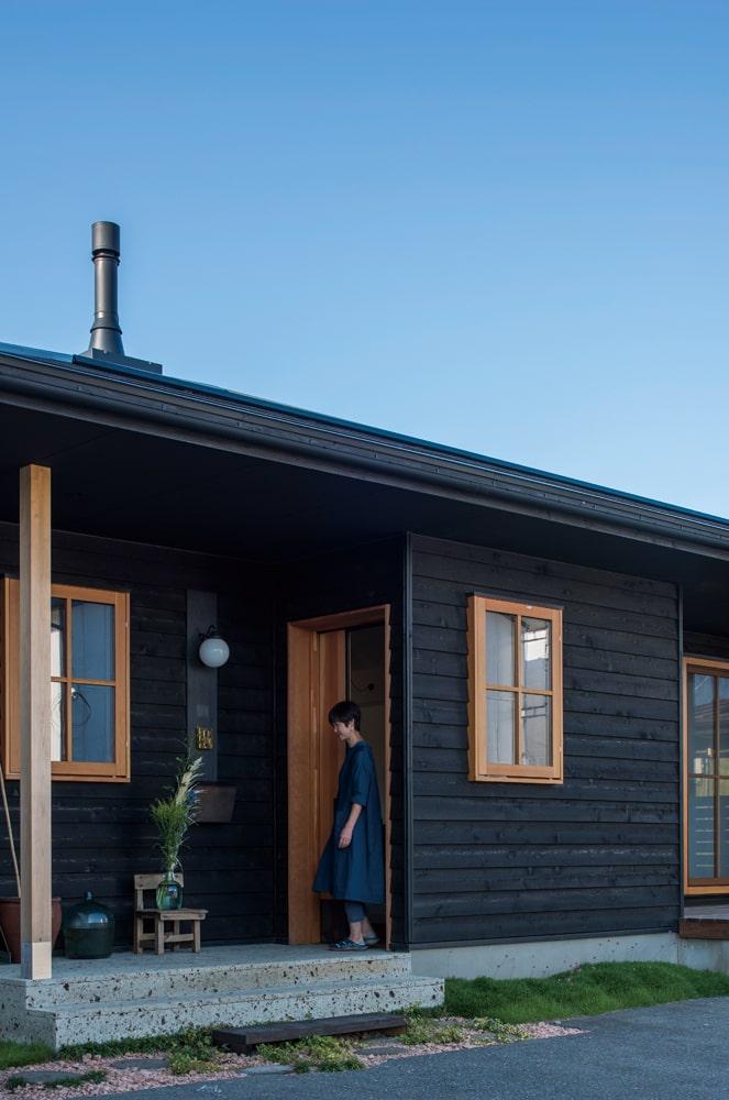 シックな黒の外壁に木製の玄関ドアや窓が映える