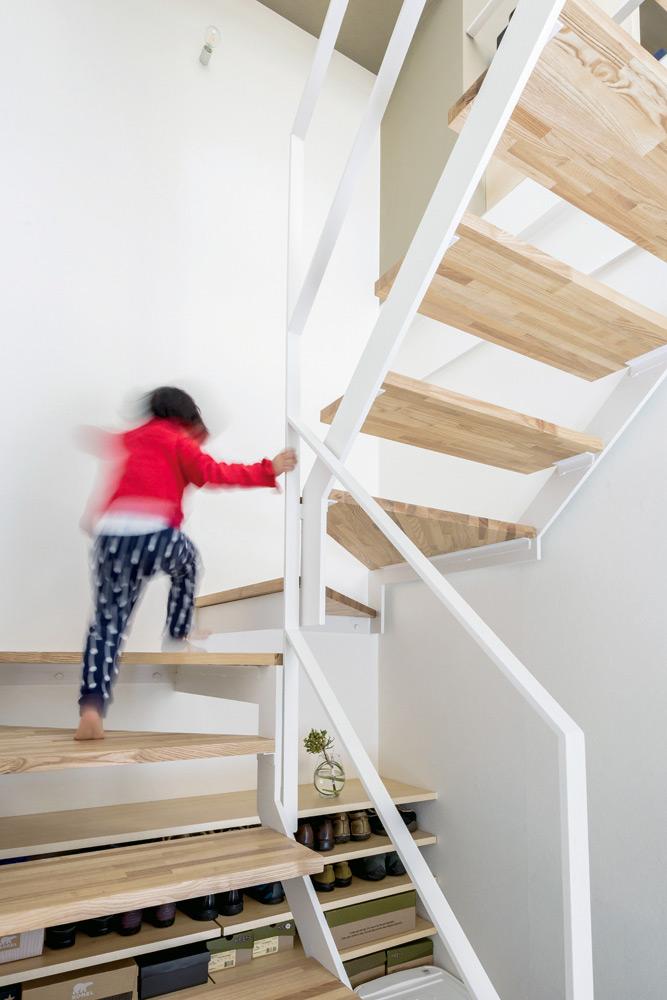 リズミカルな鉄骨階段が、1階の玄関から2階の居住スペースへと誘う。涼しい玄関の土間は、暑さが苦手な犬たちのお気に入りの寝床に