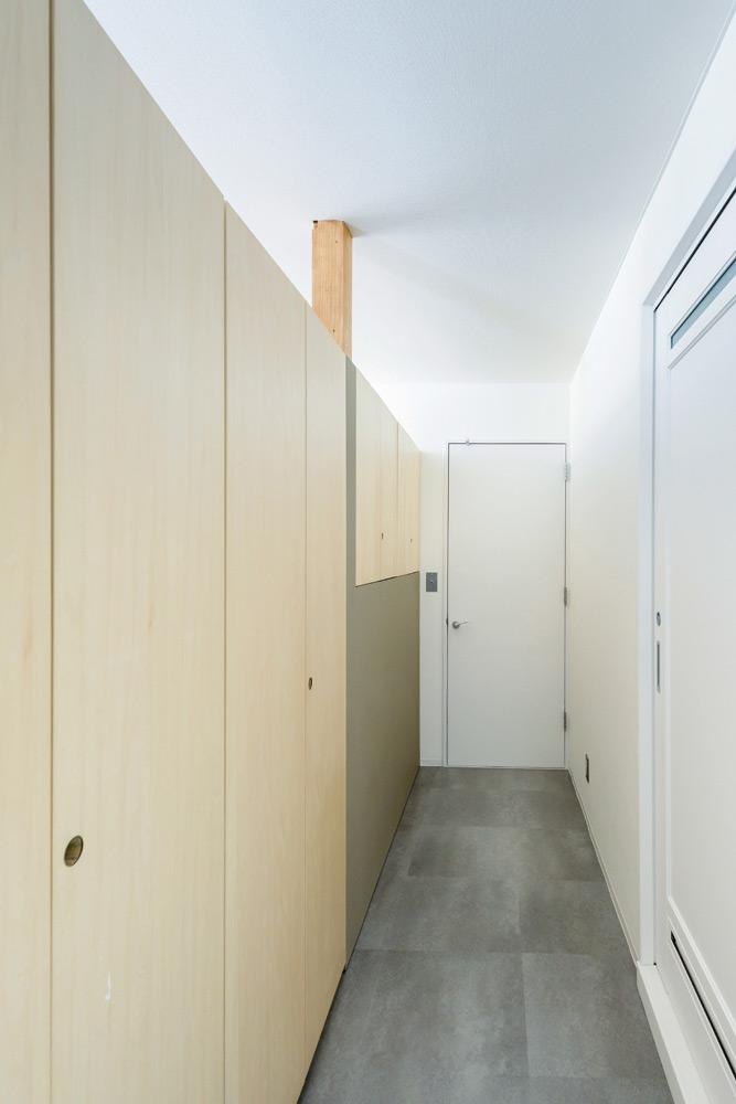 キッチンから寝室につながる廊下の左手には造作収納。壁面を有効活用して、収納が少ないという悩みを解消した。右側は、既存の設備を生かした水まわり