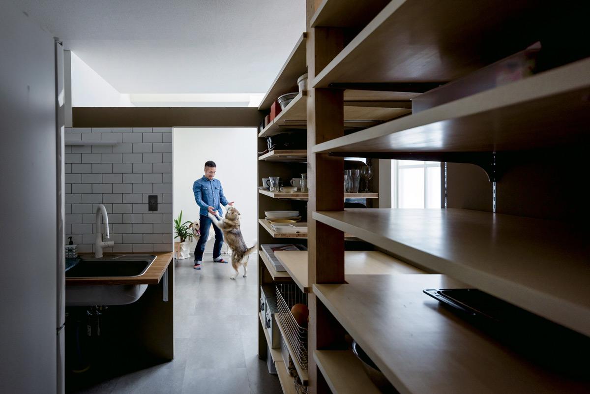 キッチンの内側には、既存の柱を生かしながら大容量の収納棚を造作。ストック食材から食器までキッチンまわりのモノがすべて収まる