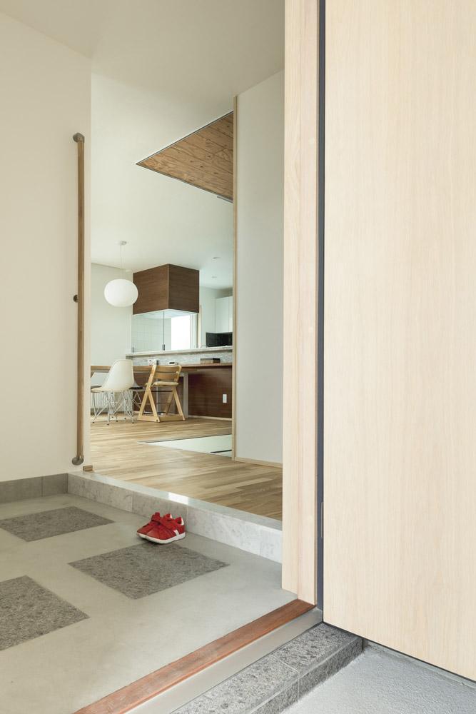 仕切りのない開放的な玄関。三和土には外玄関と揃えた御影石をアレンジしてモダンなデザイン