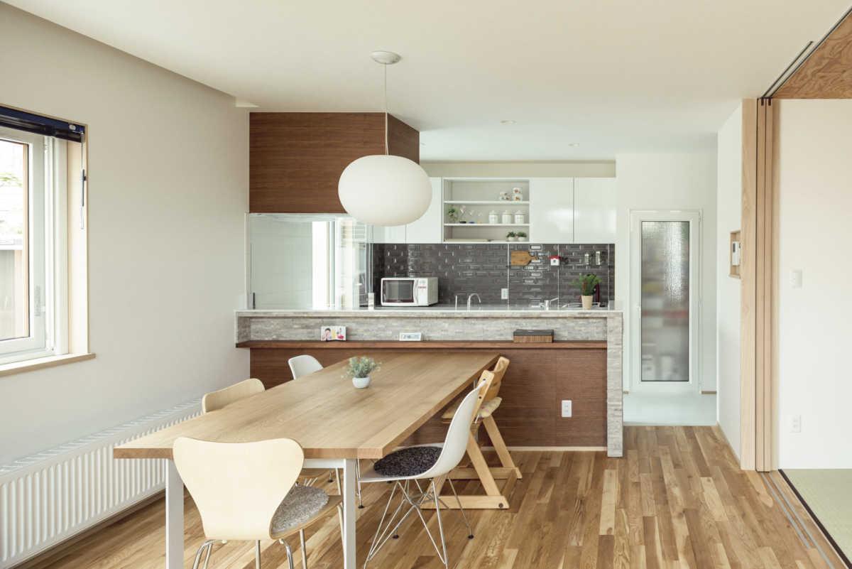 いつでも家族の顔を見ながら家事ができる対面キッチンと広いダイニングは家族団らんの場。キッチンの側面には石素材、作業台の壁には輸入タイルを使ってメンテナンスフリーで耐久性も高く