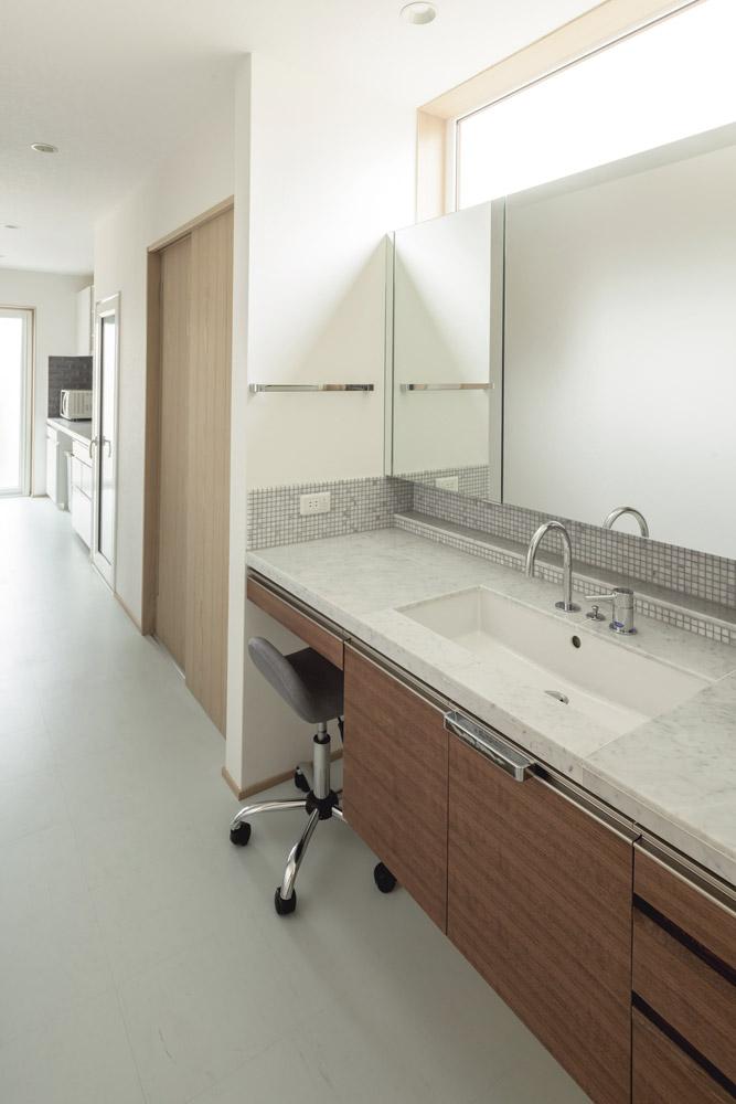 造作した洗面台は横幅も広く、壁いっぱいの鏡が便利。椅子を置いてメイクスペースも設けた