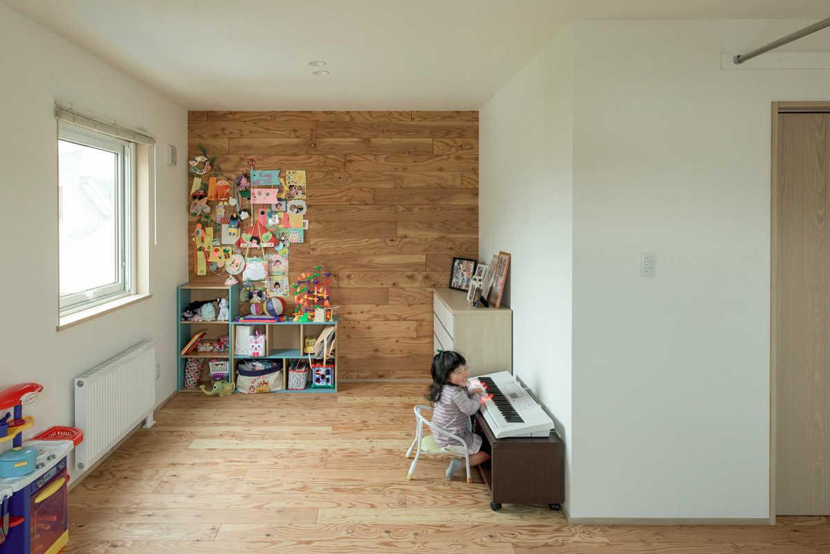 子ども部屋は床にも壁にも構造材の合板を使用。壁には思い出の写真や絵を直接貼って