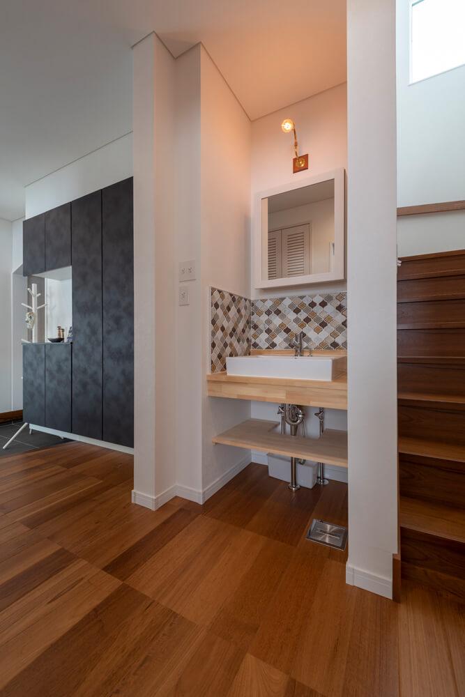 2階へ上がる階段脇にコンパクトな洗面コーナーを設置。この1階の右手奥には主寝室や子ども部屋がある