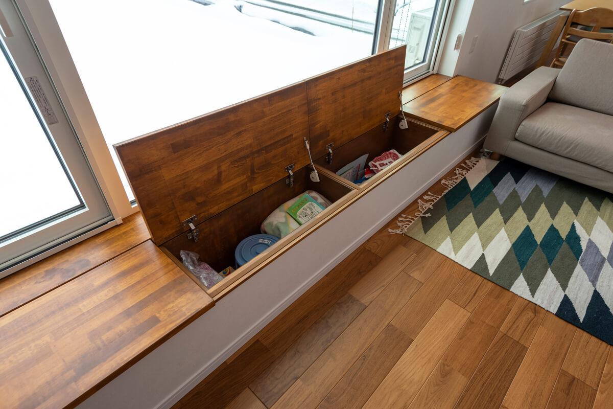 奥羽山脈を見渡せるリビングの窓下に設けたベンチは、ソフトダウンの棚板の収納スペースに。使い勝手に考慮した造作家具のよさ