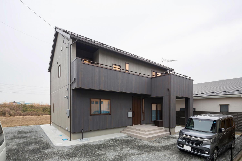 洋瓦の屋根と外壁をブラックで統一したモダンな外観。リビングとユーティリティからバルコニーへ出られるようになっている