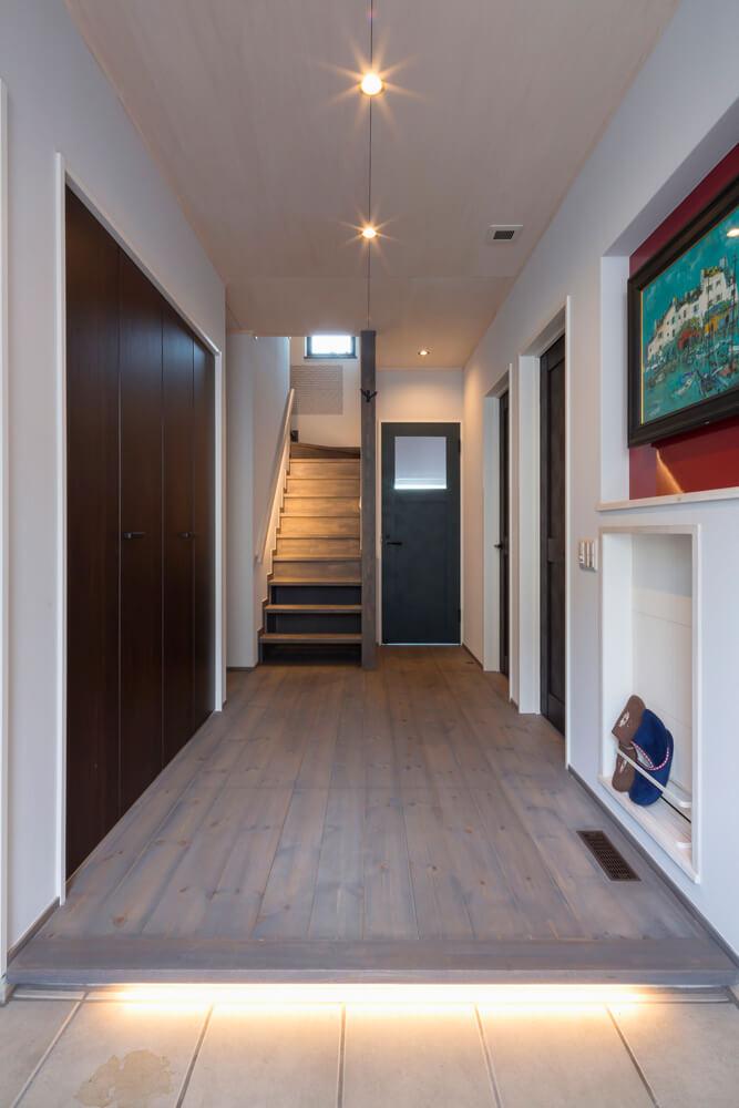 間口の広い玄関ホールから2階リビングへ。照明は人感センサー式なので両手がふさがっていても安心だ