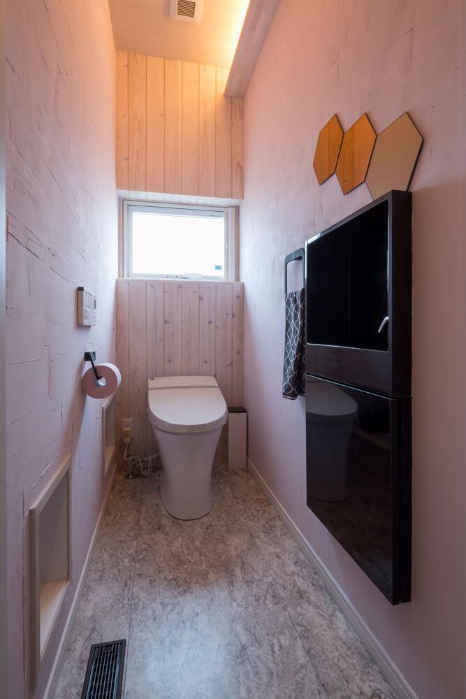トイレは1階、2階で内装を変えることで表情に変化をつけている。階段下を有効活用した収納(写真左手)もある