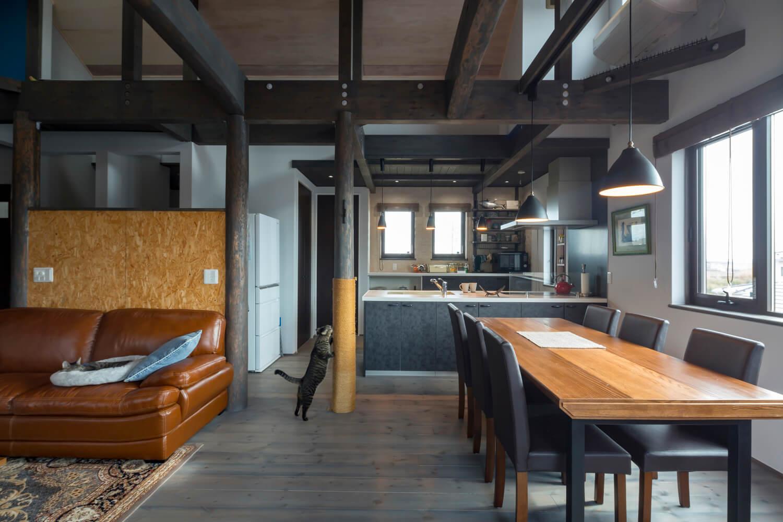 バルコニーからリビング・キッチンを望む。チャコールグレーに塗られた床と柱が長年使い込まれたような風合いを醸し出す