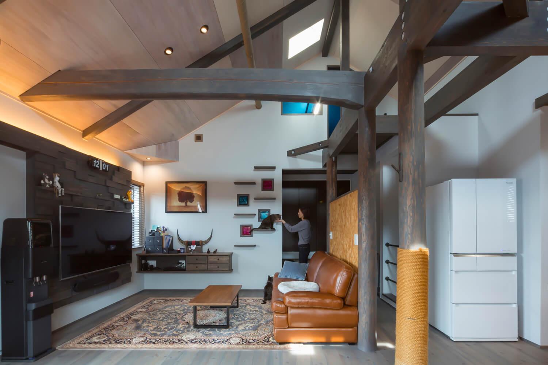 リビングのアクセントウォールと壁面収納は造作によるもの。壁面のキャットウォークは桁と梁へ上がれるようになっている