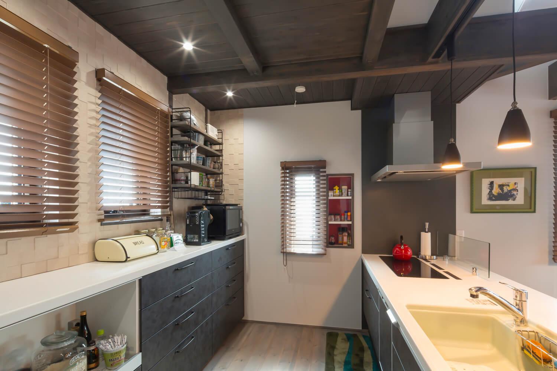 奥さんこだわりのキッチンは圧迫感が出ないように飾り棚でおしゃれに。窓の向こうは遮るものがなく、朝陽が部屋の奥まで射し込む