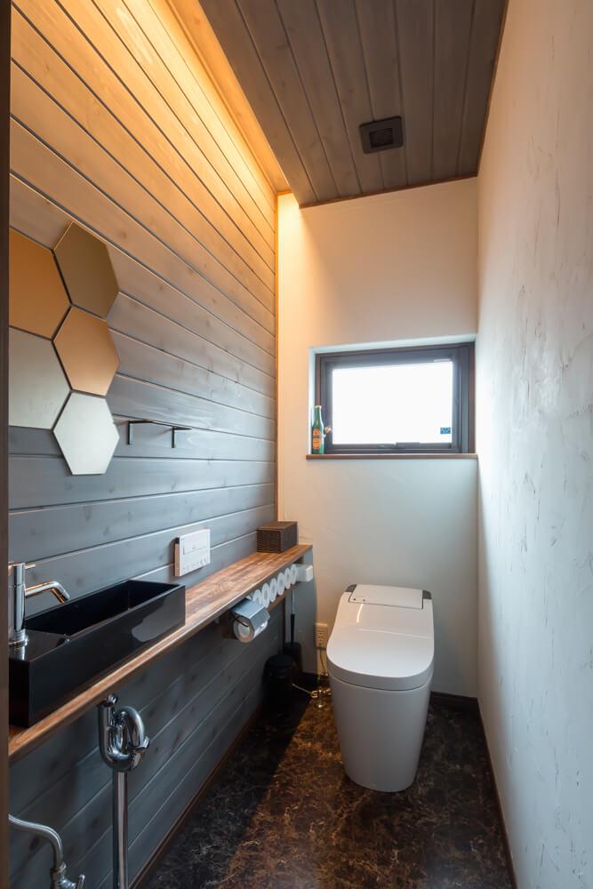 2階トイレはダークトーンでまとめている。ご夫妻が大型家具店や通販で揃えたというインテリアをセンス良くレイアウト