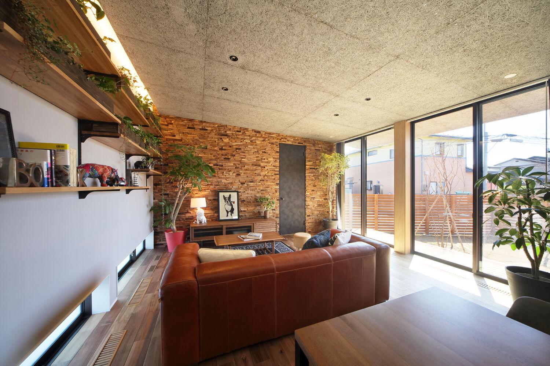 リビングの北面には地窓を設け、風の通り道を確保。緩やかな勾配天井はインダストリアルな趣の木毛セメント板仕上げ