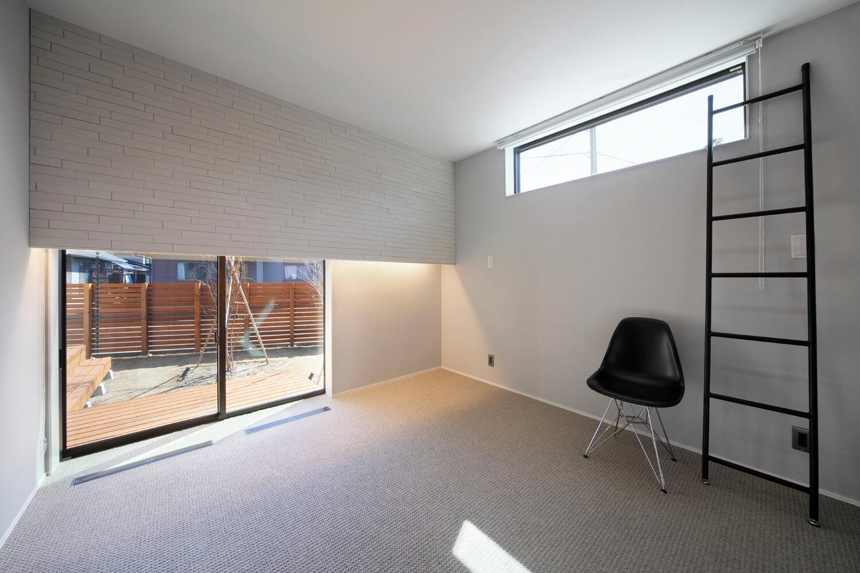 地窓から庭が見渡せる寝室。暖房は床下吹き出し式エアコン空調を採用しており、ガラリを通して暖気が室内に行き渡る