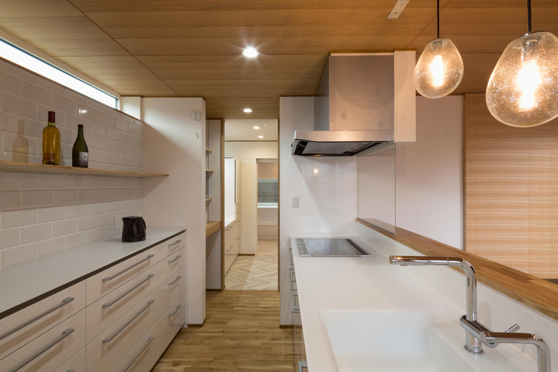 キッチン、ユーティリティ、浴室を直線上に配置。ユーティリティから玄関につながる回遊型の間取り