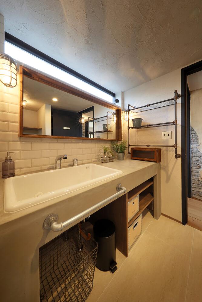 モルタルで造作した洗面台。壁にはレンガ調タイルをあしらい、明かり採りの高窓も取り入れた