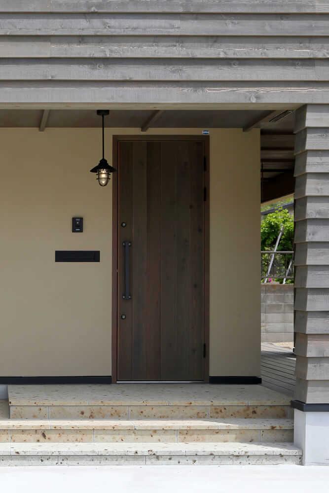 西面の玄関ポーチ部分は凹ませ、雨に濡れないよう配慮。バイクガレージも設けられている