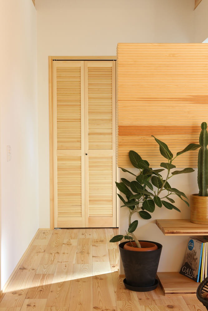 玄関は仕切らずリビングからの広がりを重視。匂いがこもらないルーバータイプの無垢建具を設置した