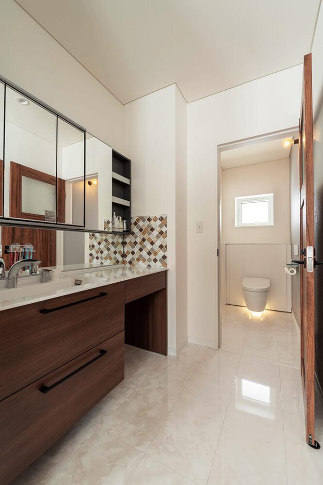 洗面コーナーはLDKと区別するため白い床材を選択。木の風合いを生かした洗面カウンターやタイルなどMさんご夫妻が厳選した素材が随所に