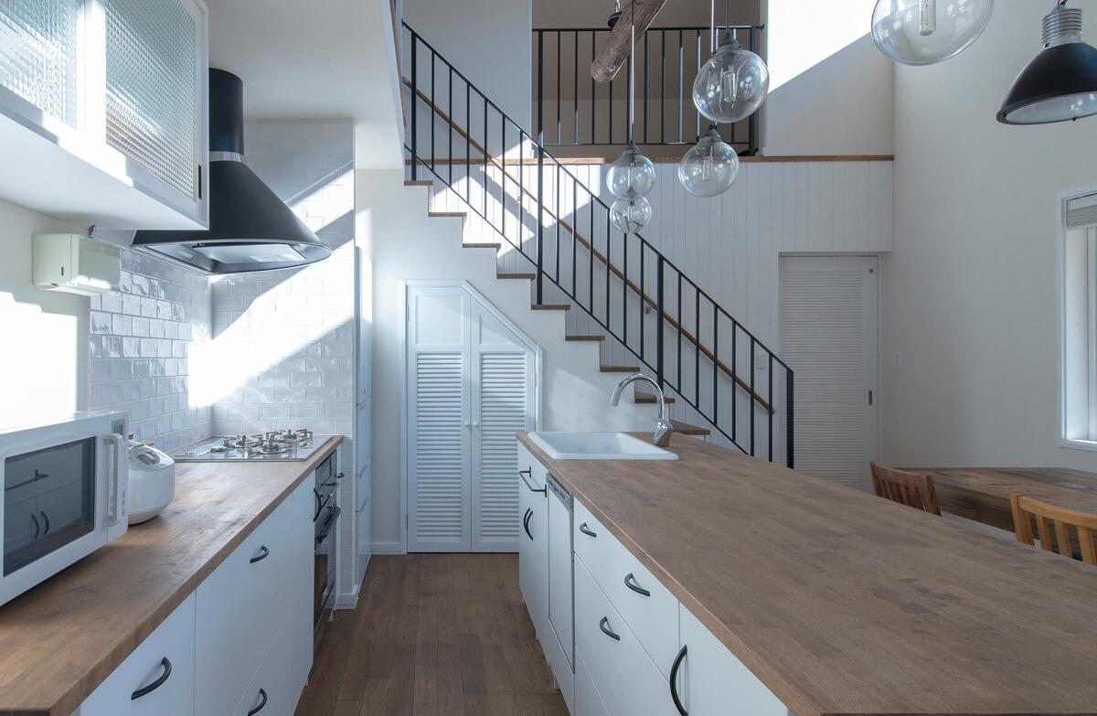 アイランドキッチンの並びに、階段下を利用したパントリーを設置。扉はLDK全体のインテリアのテイストに合わせてデザインされている