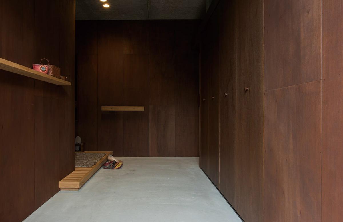 ゆったりと広い玄関は、ラワン合板と木毛セメント板というラフな素材で構成。右奥に行くとアジト