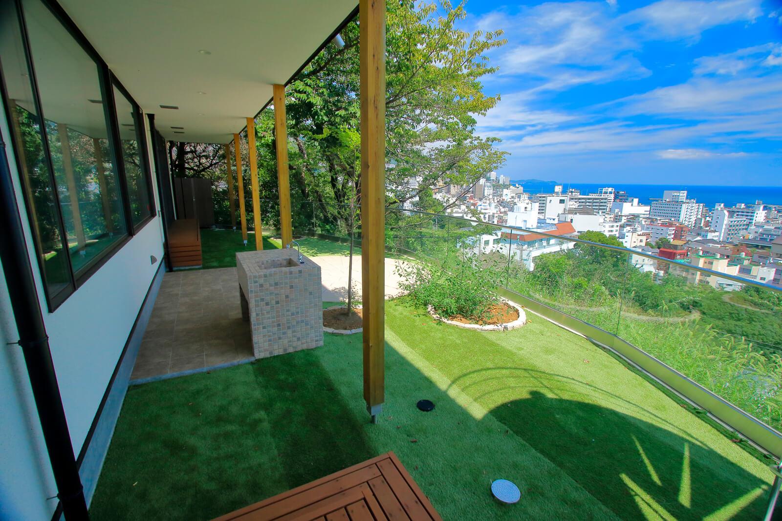 庭の向こうには豊かな緑に囲まれた景観と、熱海の街 並みと海を見晴らす絶景が広がる