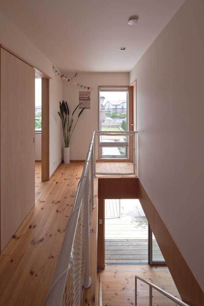 寝室や個室などプライベートな居室を配置した2階。廊下からも階下のデッキが見え、外部の様子がそれとなく伝わってくる