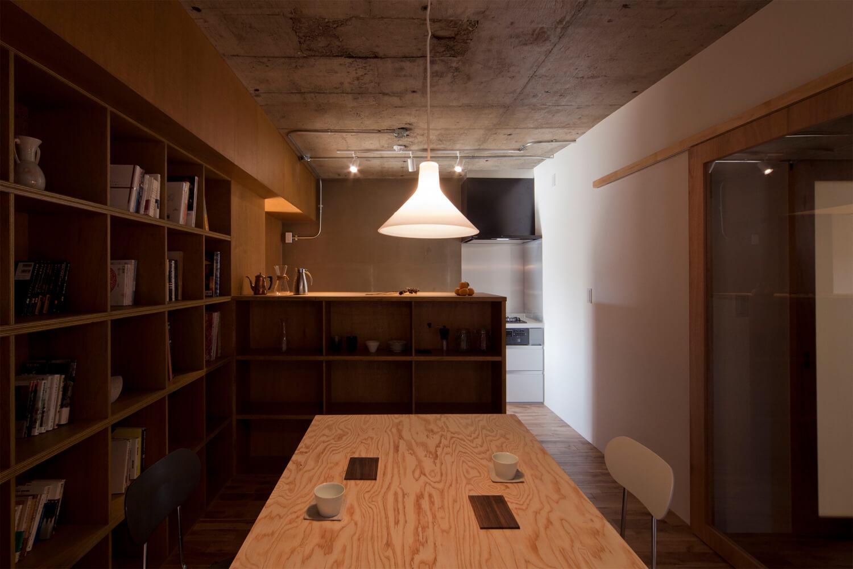 本棚、収納で緩やかに区切られたダイニングとキッチン